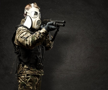 portrait of young soldier with gas mask aiming with shotgun against a grunge wall photo