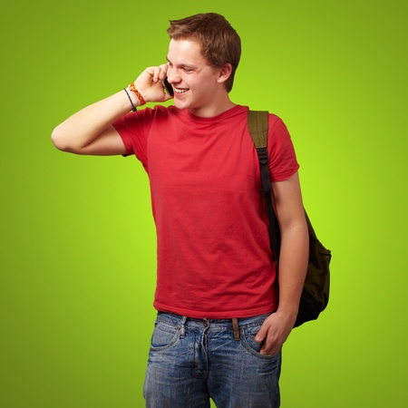 portrait of young man talking on mobile over green background photo