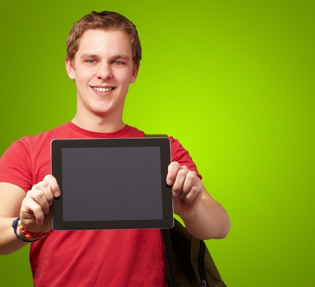 portrait of young man holding a digital tablet over green background photo
