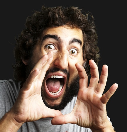 portrait of young man screaming against a black background photo