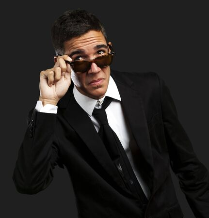 portrait of business man taking off the sunglasses against a black background photo