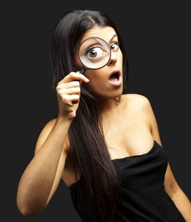 portrait of young woman surprised looking through a magnifying glass over black Stock Photo - 12656680