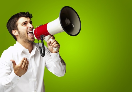 portrait of young man shouting with megaphone over green background photo