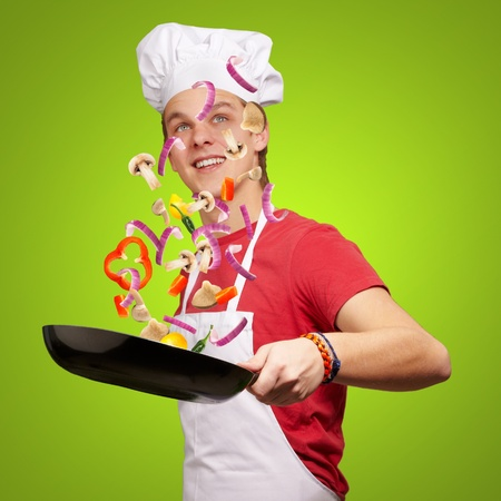 portrait of young cook man cooking vegetables on pan over green background photo