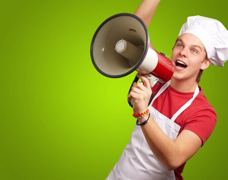 portrait of young cook man shouting with megaphone over green background photo