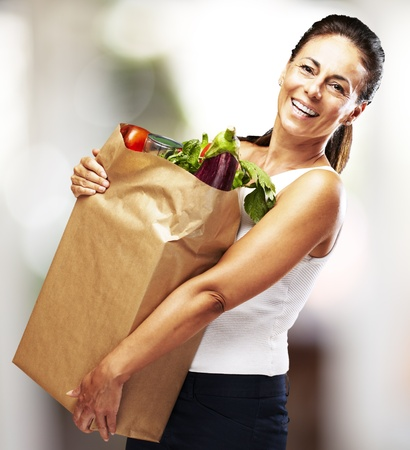 portrait of a middle aged woman smiling and carrying the purchase indoor photo