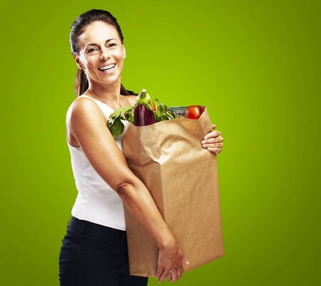 portrait of middle aged woman holding the purchase over green background photo