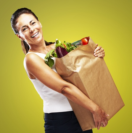 bolsa de pan: retrato de una mujer de mediana edad la celebración de la compra sobre fondo amarillo