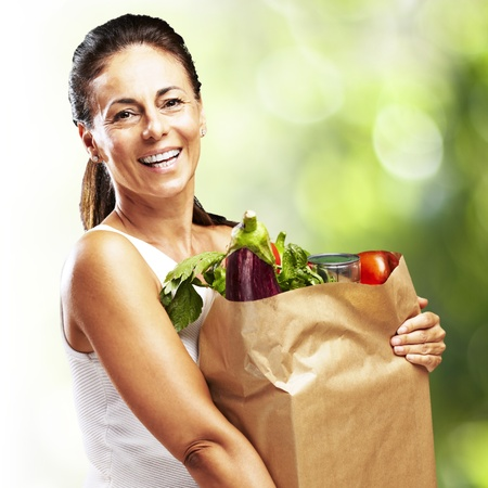 beautiful middle aged woman: woman with purchase against a nature background