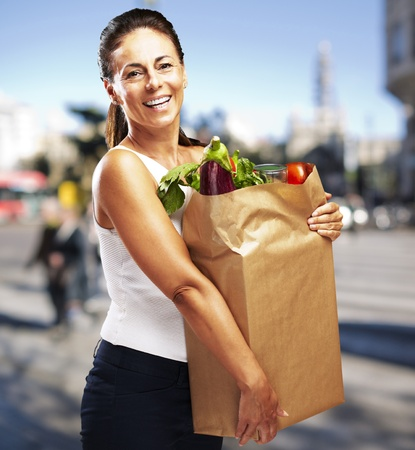 young woman holding a grocery bag against a street background photo