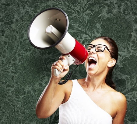 woman shouting: portrait of middle aged woman shouting using megaphone against a vintage wall Stock Photo