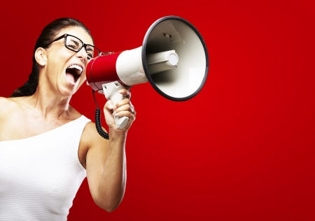 portrait of middle aged woman shouting using megaphone over red background photo
