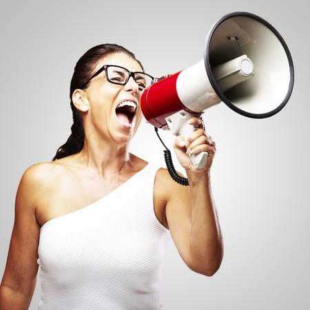 Porträt von Frau mittleren Alters mit Megaphon schreien über grauem Hintergrund Standard-Bild