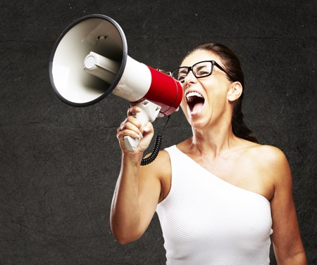 loudspeaker: portrait of middle aged woman shouting using megaphone against a grunge wall