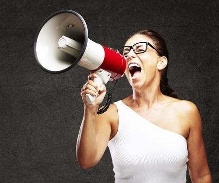 megafono: retrato de una mujer de mediana edad gritando con el meg�fono contra la pared del grunge