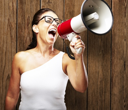 portrait of woman shouting with megaphone against a wooden wall Stock Photo - 12656761