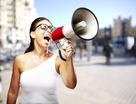 young woman shouting through a megaphone against a street background photo