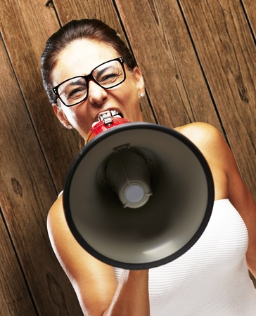 woman screaming: portrait of woman shouting with megaphone against a wooden wall Stock Photo