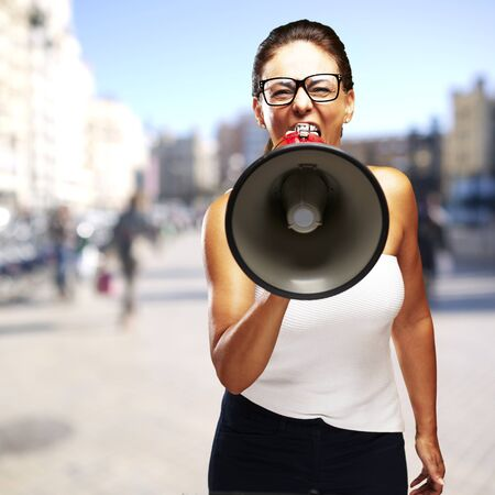 young woman shouting through a megaphone against a street background Stock Photo - 13486318