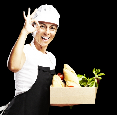 portrait of middle aged woman carrying groceries in a box over black photo