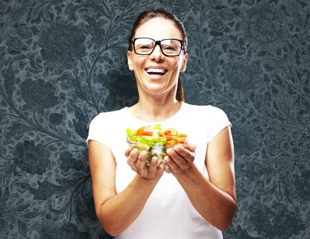 portrait of middle aged woman holding salad against a vintage wall photo