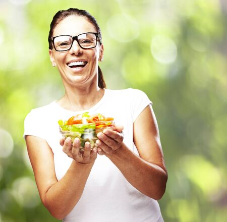 portrait of middle aged woman holding salad against a nature background Stock Photo - 12656738