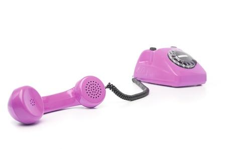 vintage purple telephone isolated over white background photo