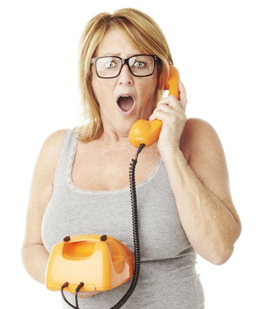 portrait of middle aged woman surprised talking on vintage telephone over white photo