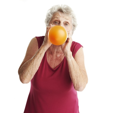inflating: portrait of senior woman blowing a balloon