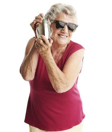 martini shaker: portrait of senior woman shaking cocktail shaker over white