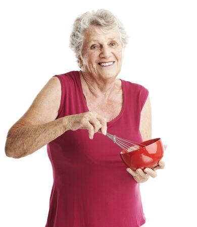 hiebe: Portr�t Senior Frau Schlagen von Eiern auf wei�em