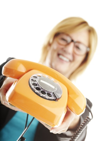 portrait of middle aged woman showing vintage telephone over white photo
