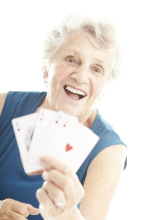 card game: portrait of senior woman showing poker cards over white Stock Photo