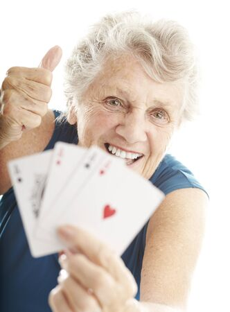 portrait of senior woman showing poker cards over white photo