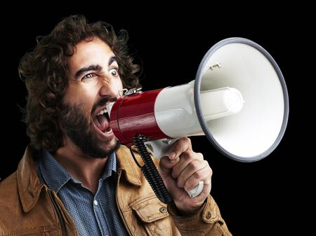 portrait of young man shouting with megaphone against a black background photo
