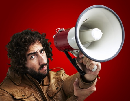 portrait of young man holding megaphone against a red background photo