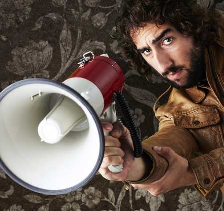 portrait of young man holding megaphone against vintage wall photo