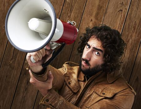portrait of young man holding megaphone against a wooden wall photo