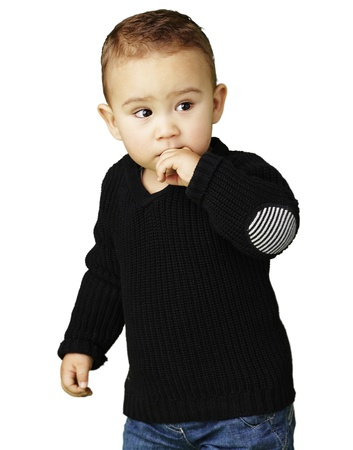 young boy thinking with his finger near his mouth against a white background photo