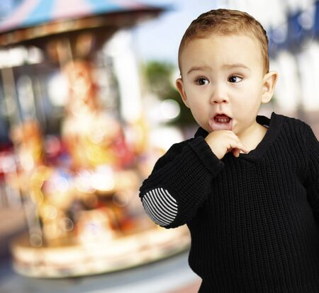 surprised young boy wearing a black jumper against a carousel background photo