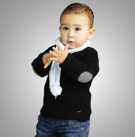 adorable boy clapping his hands against a grey background photo