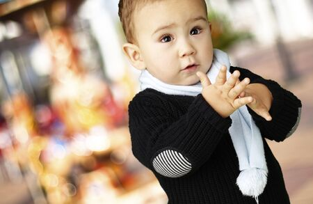 adorable boy clapping his hands against a carousel background photo