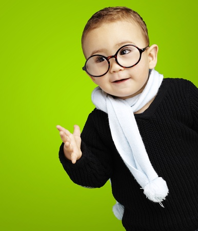 wearing glasses: happy young boy wearing round glasses against a green background Stock Photo