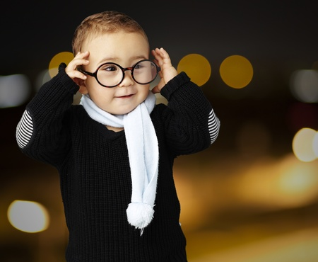 happy young boy wearing round glasses against a city by night photo