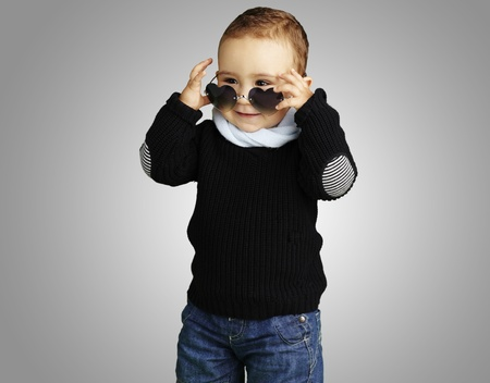 happy young boy wearing heart sunglasses against a grey background photo