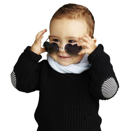 joking: happy young boy wearing heart sunglasses against a white background
