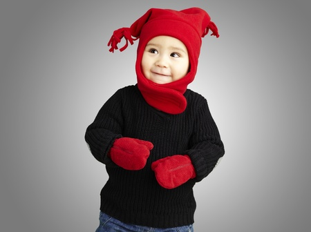 young happy boy wearing red winter accessories against a grey background photo