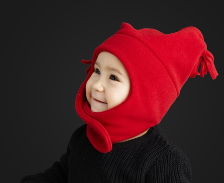 young happy boy wearing red winter accessories against a black background photo