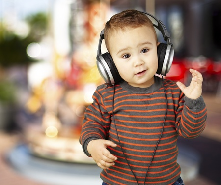 boy wearing headphones and looking confused against a carousel background photo