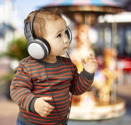 young boy wearing headphones and listening to music against a carousel background photo